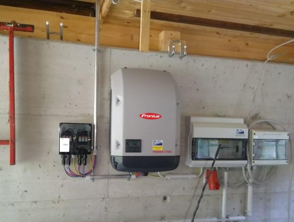 Großer Wechselrichter mit Verteilerschränken auf einer Betonwand.